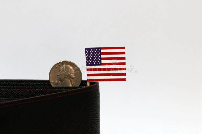 A quarter of US Dollar coins on obverse USD and mini USA flag stick on the black wallet with white background. Concept of finance or currency stock image