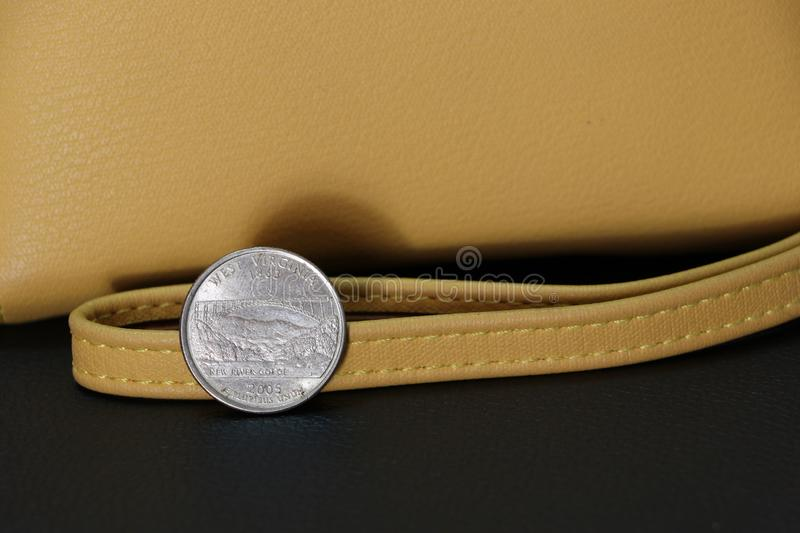 A quarter of US Dollar coins on reverse USD with sand color wallet on black floor royalty free stock images