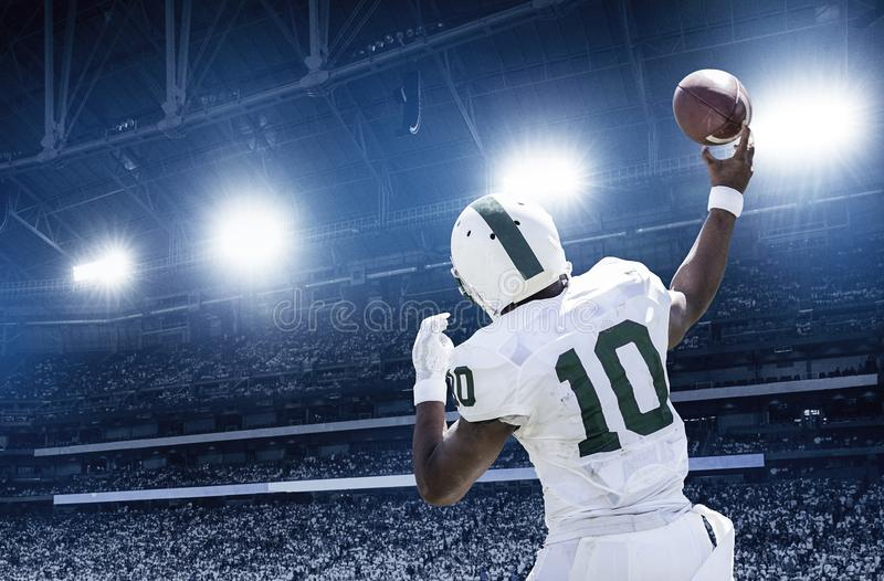 Quarterback throwing a football in a professional football game stock photography