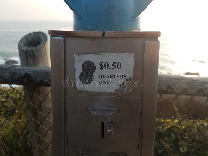 Quarters only 50 cents sign on metal machine. Near water stock image