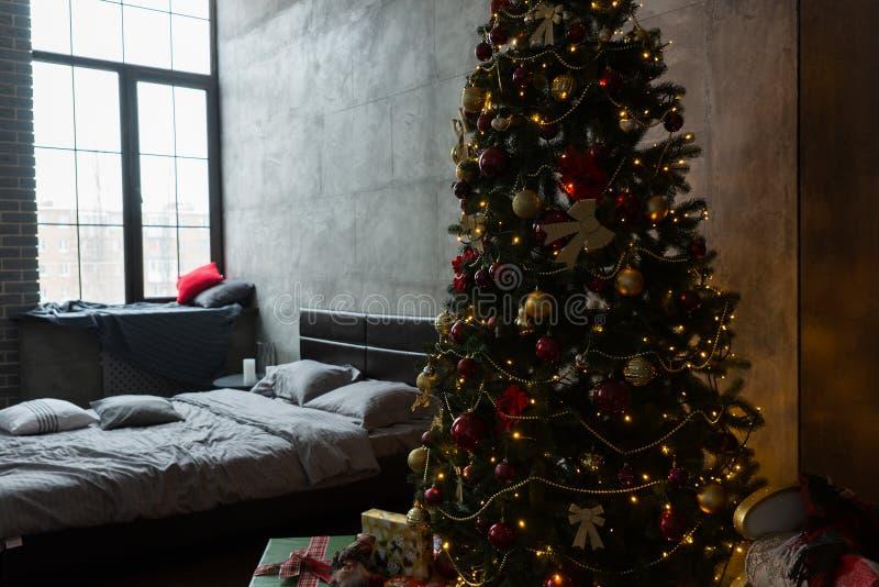 Quarto à moda com cama moderna e grande árvore de Natal com a fotos de stock
