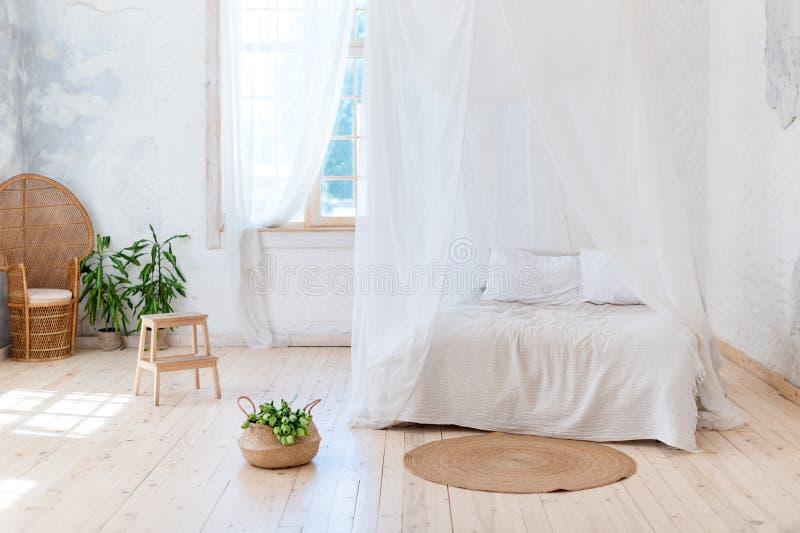 Quarto acolhedor em cores claras com um assoalho de madeira, uma grande cama de quatro colunas, a cadeira de vime e a cesta das f fotografia de stock