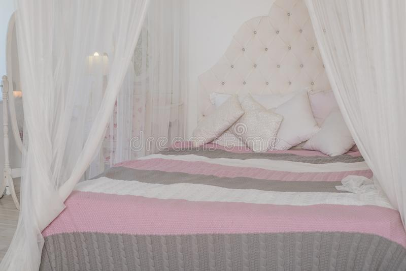 Quarto acolhedor em cores pastel claras, uma grande cama de quatro colunas com descansos Projeto escandinavo da simplicidade Sótã fotografia de stock