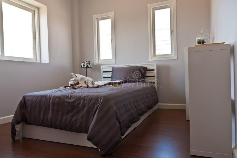 Quarto branco com a cama marrom da folha fotografia de stock royalty free