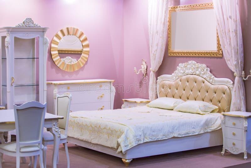 Quarto branco e cor-de-rosa luxuoso no estilo antigo com decoração rica Interior de um quarto clássico do estilo no apartamento l imagem de stock