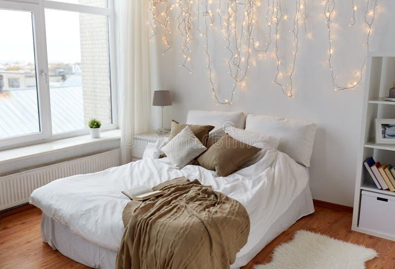 Quarto com cama e festão do Natal em casa fotografia de stock