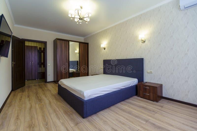 Quarto com cama no novo apartamento A cama foi feita de forma negligente Janela, wallpaper bluish shade com padrão ondulado, TV foto de stock royalty free