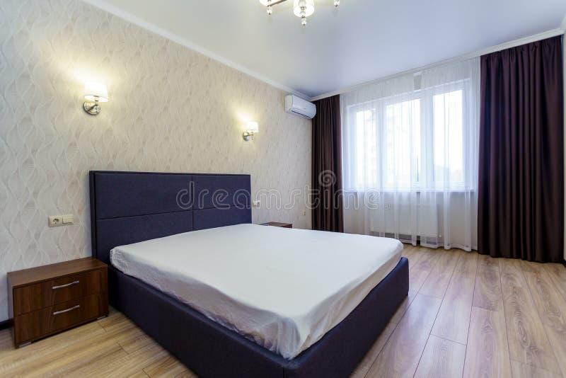 Quarto com cama no novo apartamento A cama foi feita de forma negligente Janela, wallpaper bluish shade com padrão ondulado, TV imagem de stock royalty free