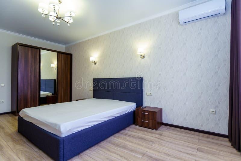 Quarto com cama no novo apartamento A cama foi feita de forma negligente Janela, wallpaper bluish shade com padrão ondulado, TV fotos de stock