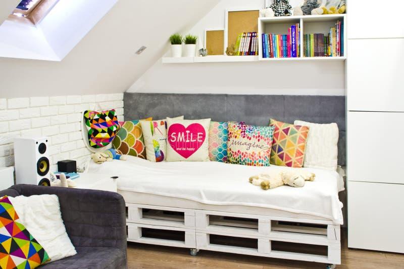 Quarto das crianças do sótão com mobília e os brinquedos coloridos imagens de stock royalty free