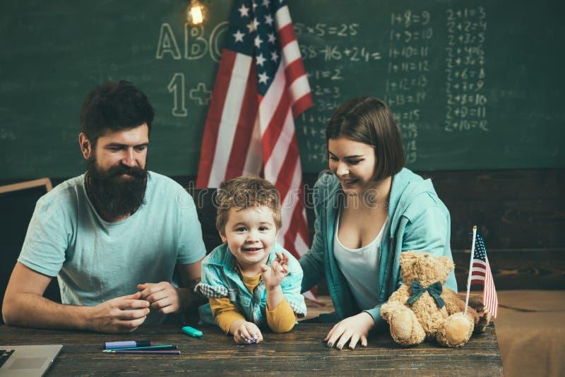 Quarto de julho A família feliz comemora o quarto de julho com as bandeiras americanas na turma escolar Quarto do dia nacional de imagens de stock royalty free