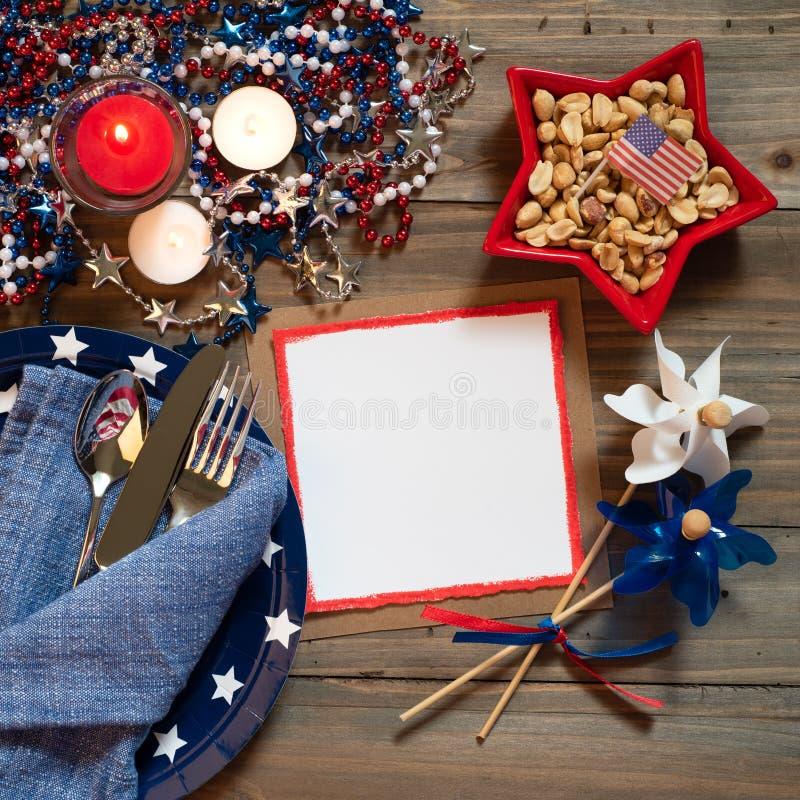 Quarto della regolazione di posto rustica della Tabella di luglio nei colori rossi, bianchi e blu con il menu o invitare carta co fotografia stock