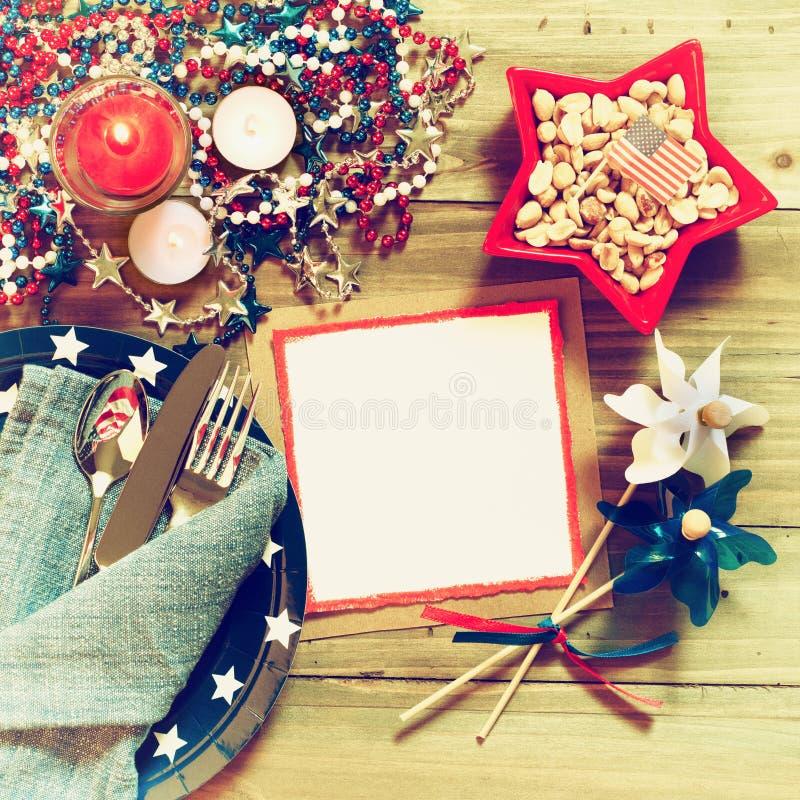 Quarto della regolazione di posto rustica della Tabella di luglio nei colori rossi, bianchi e blu con il menu o invitare carta co fotografia stock libera da diritti