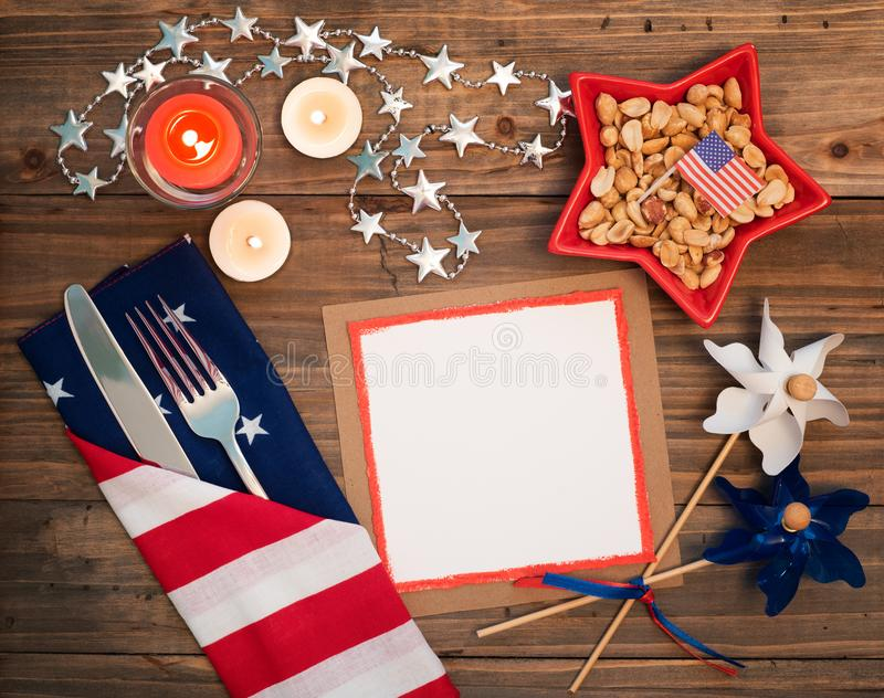 quarto della regolazione della Tabella di luglio con il tovagliolo della bandiera, l'argenteria, le decorazioni e una carta bianc fotografia stock