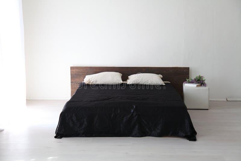 Quarto e cama brancos interiores com folhas pretas fotografia de stock