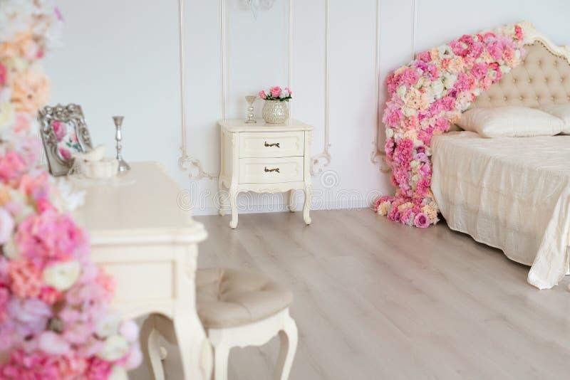 Quarto em cores de luz suave Cama de casal confortável grande decorada com as flores no quarto clássico elegante imagens de stock