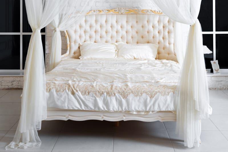 Quarto em cores de luz suave Cama de casal confortável grande de quatro cartazes no quarto clássico elegante Branco luxuoso com o imagem de stock royalty free
