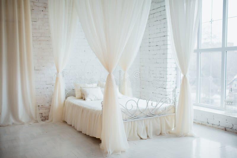 Quarto em cores de luz suave Cama de casal elegante confortável grande no interior branco do sótão do tijolo com grande janela imagem de stock