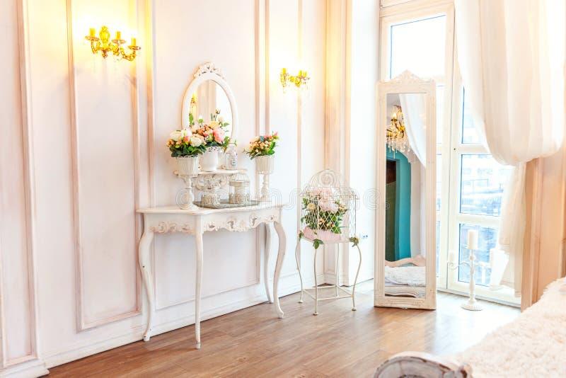 Quarto interior limpo brilhante branco do clássico luxuoso bonito no estilo barroco com espelho, tabela, a grande janela, e a flo fotos de stock royalty free