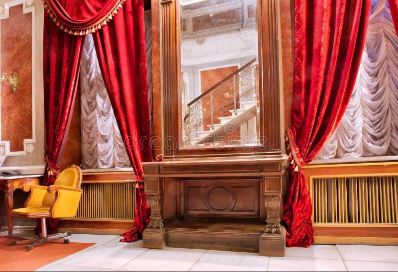 Quarto luxuoso com o espelho vermelho das cortinas n fotografia de stock