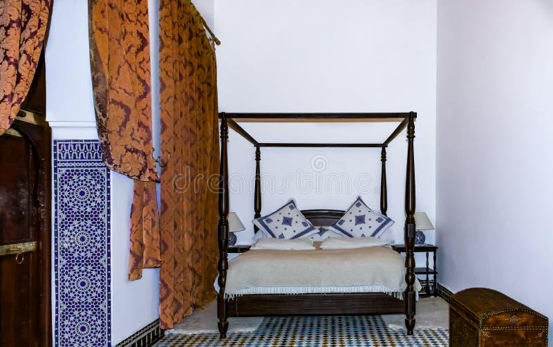 Quarto marroquino tradicional com uma cama do dossel e mosaico em um r imagens de stock royalty free