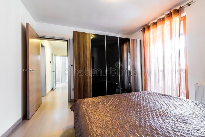 Quarto moderno do hotel com cama e armário imagem de stock royalty free