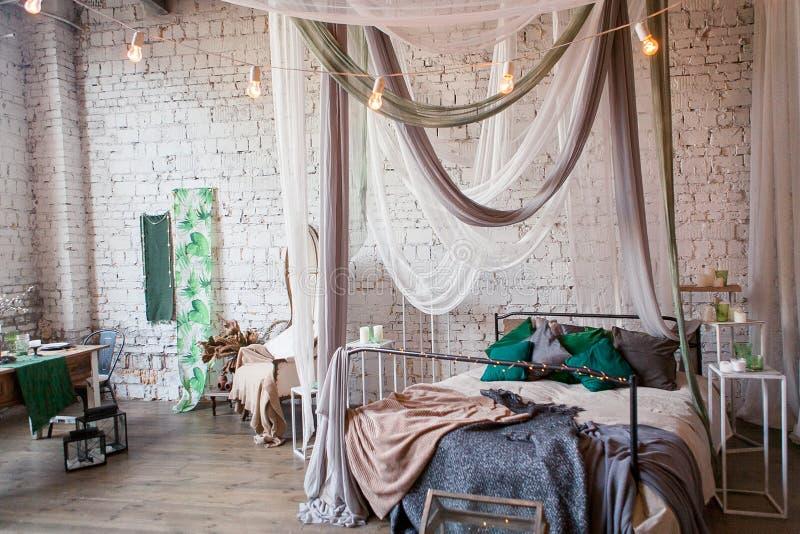 Quarto moderno do sótão com teto alto, parede de tijolo, assoalho de madeira, armário de madeira, acessórios do projeto na pilha  foto de stock