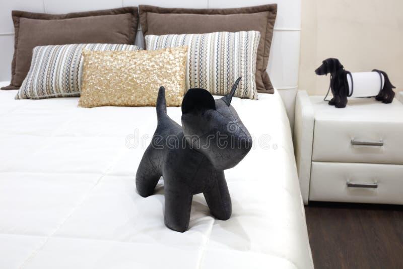 Quarto moderno luxuoso do estilo com o cão preto do brinquedo e os descansos diferentes na cama branca, interior de um quarto do  fotos de stock