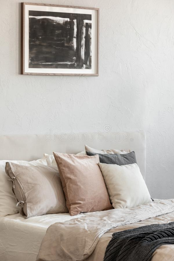 Quarto na moda com a cama enorme confortável na foto lisa, real moderna imagens de stock royalty free
