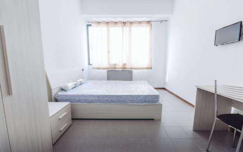 Quarto simples do dormitório do estudante-estilo com lotes da luz foto de stock royalty free