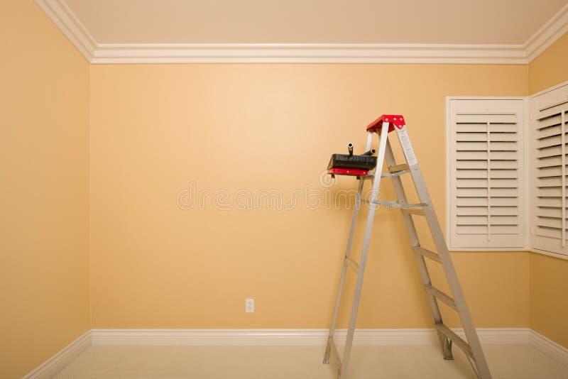 Quarto vazio com escada, bandeja da pintura e rolos imagem de stock royalty free
