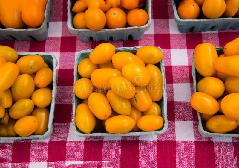 Quartos de tomates amarelos ovais em uma toalha de mesa vermelha e branca do tabuleiro de damas imagem de stock