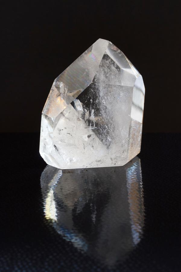 Quartz crystal mineral shows its optical properties with light refraction on black background with reflection stock photography