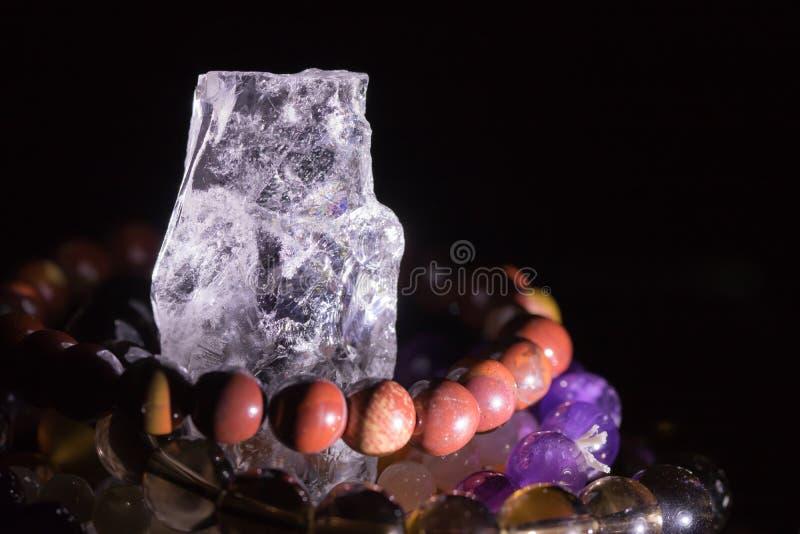 Quartz geode with semiprecious gemstone bracelets charging, spirituality concept, alternative medicine. Healing, on black background with copy space royalty free stock photos