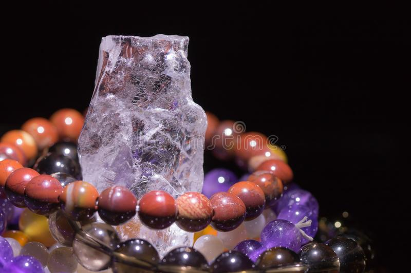 Quartz geode with semiprecious gemstone bracelets charging, spirituality concept, alternative medicine. Healing, on black background with copy space royalty free stock image