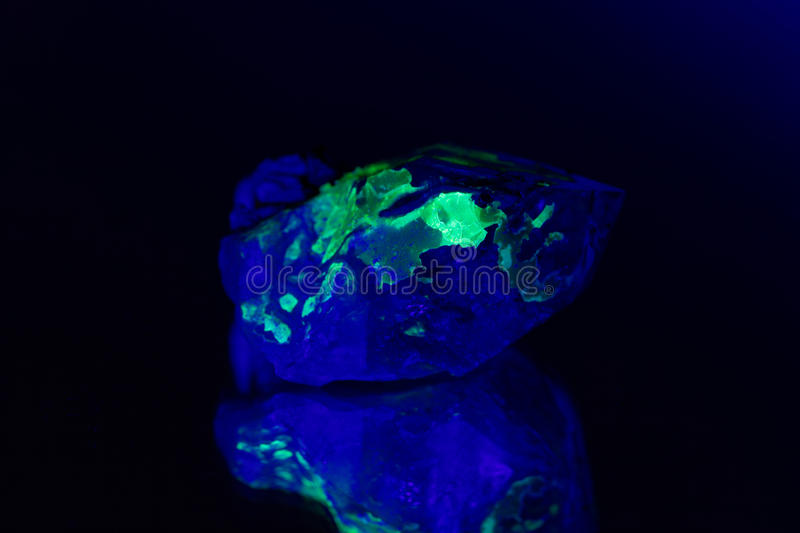 Quartz with a green fluorescent hyalite cover royalty free stock photography