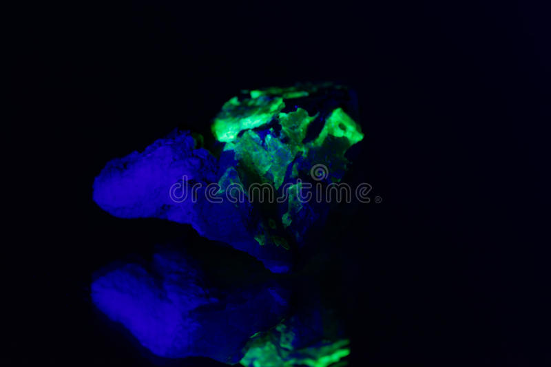 Quartz with a green fluorescent hyalite cover royalty free stock photo