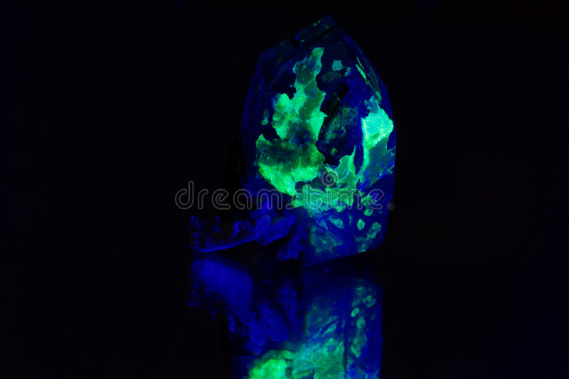 Quartz with a green fluorescent hyalite cover stock photos