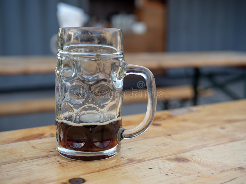 Quasi svuoti la tazza di birra tedesca che si siede sulla tavola fotografia stock