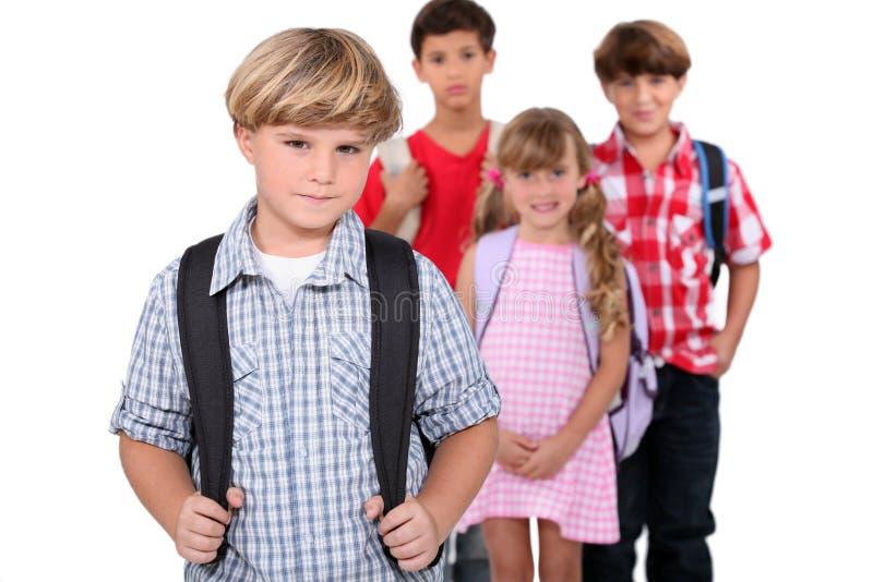 Quatre écoliers avec des sacs à dos images libres de droits