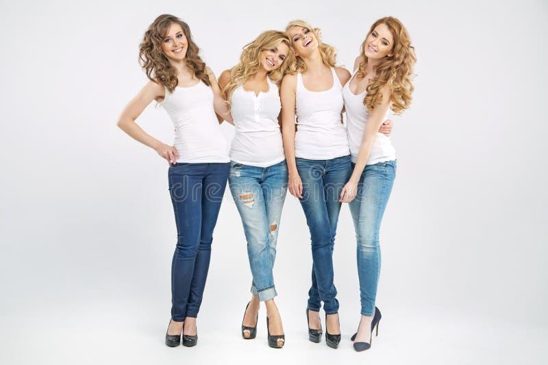 Quatre amies attirantes dans l'étreinte images stock