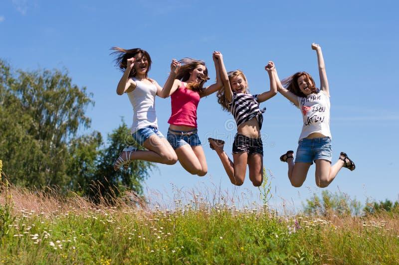 Quatre amies de l'adolescence heureux sautant haut contre le ciel bleu photographie stock libre de droits