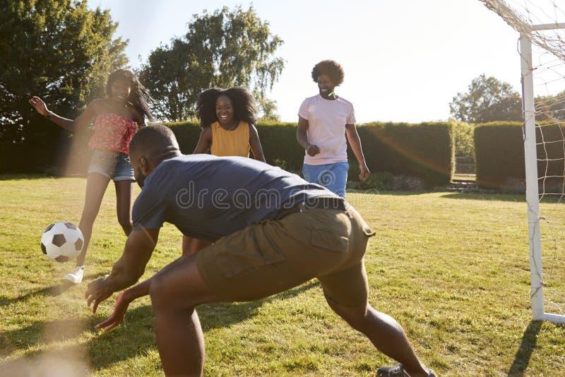 Quatre amis adultes noirs ayant un jeu fun du football photo stock