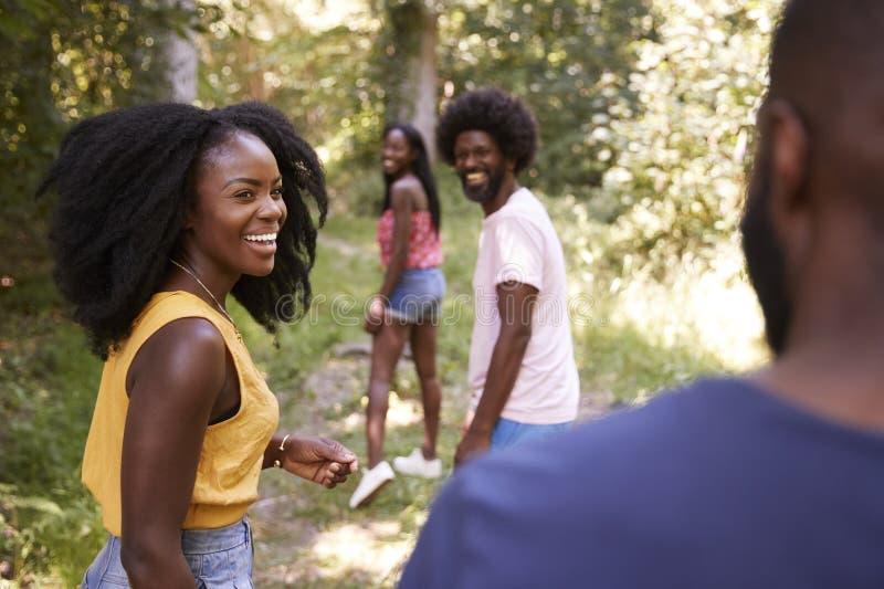 Quatre amis adultes noirs marchant dans une forêt, fin  images libres de droits