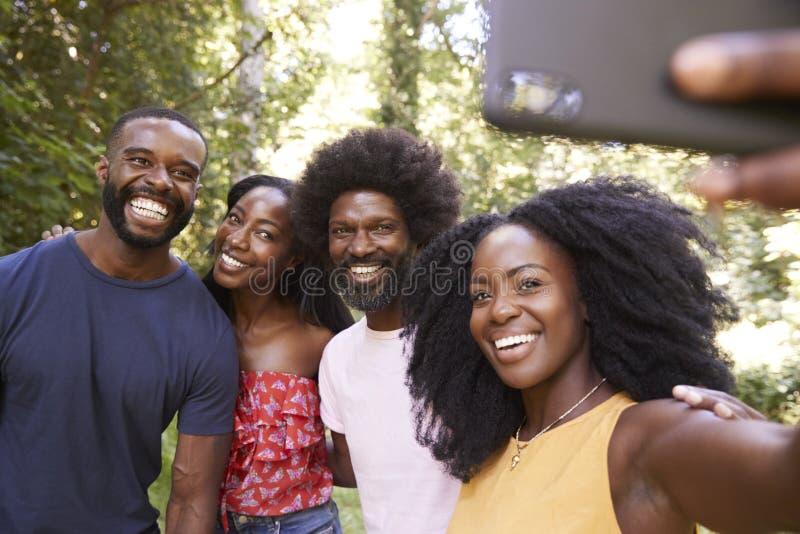 Quatre amis adultes noirs prennent un selfie pendant une hausse de forêt image stock