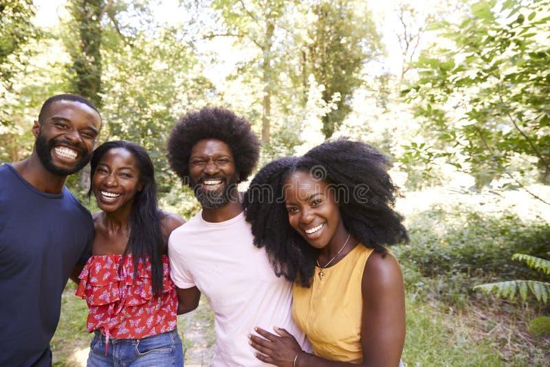 Quatre amis adultes noirs sur une promenade dans la forêt, portrait images stock