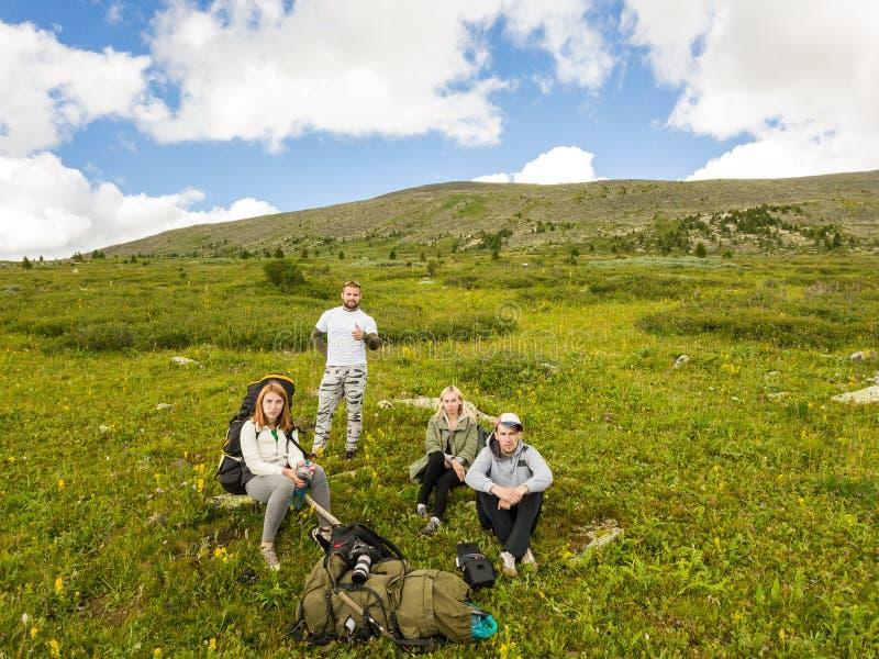 Quatre amis des touristes, filles et garçons, avec les sacs à dos et la came images libres de droits