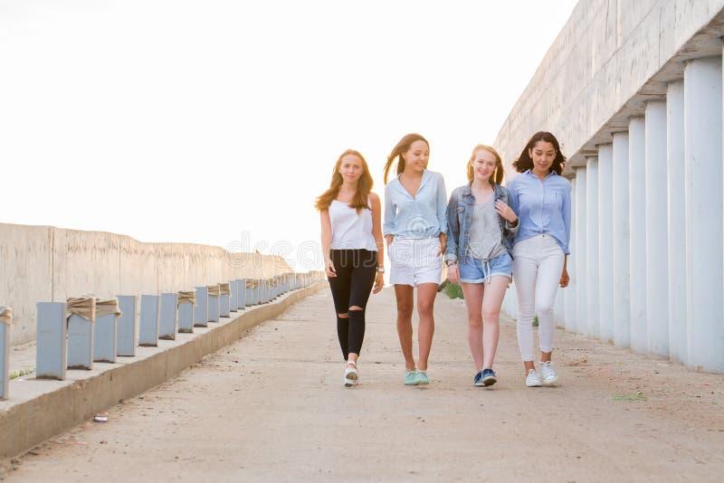 Quatre amis féminins marchant vers le bas au passage couvert, fond de soleil photos stock