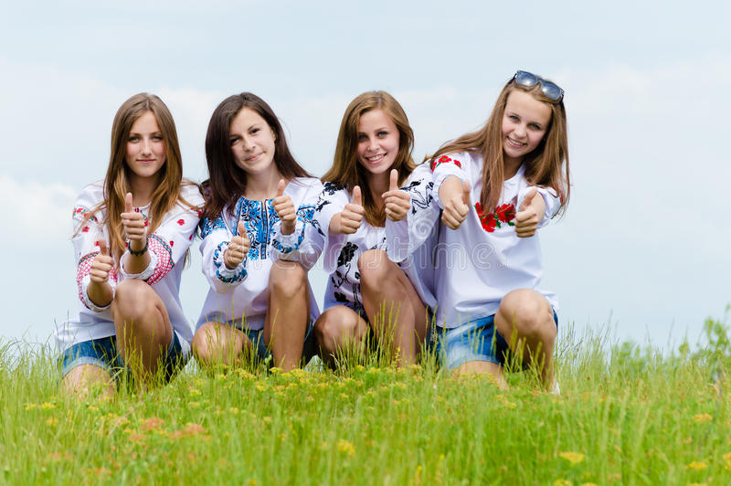 Quatre amis heureux de jeunes femmes montrant des pouces dans l'herbe verte au-dessus du ciel bleu image libre de droits