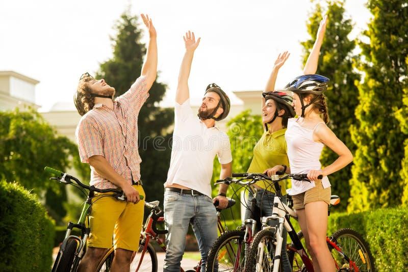 Quatre amis heureux se reposant dehors image libre de droits